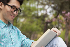 Young man with glasses smiling and enjoying his book, outdoors in a park Stock Photo