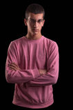 Young man with glasses standing with arms crossed on black backg Royalty Free Stock Photo