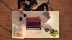 Young man in glasses and suit coming in, drinking coffee and working on laptop, sitting behind desk, top shot stock footage