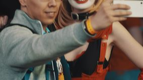Young man in glasses takes selfie with girl in Harley Quinn character costume stock footage