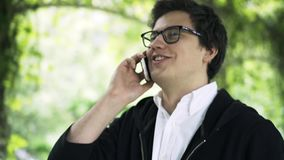 Young man in glasses is talking on his phone and walking in a park, side view stock footage