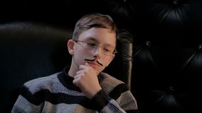 A young man with glasses and a thin mustache sits in a black leather chair. A smart guy holds his hand at his chin and ponders. A smart guy holds his hand at stock video footage