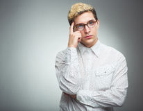 Young man with glasses thinking Stock Photography