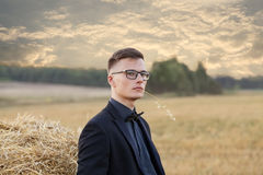 Young man with glasses thinking and standing on the field Royalty Free Stock Photos