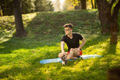Young man in glasses training yoga outdoors. Sporty guy makes relaxing exercise on a blue yoga mat, in park. Copy space.  stock images