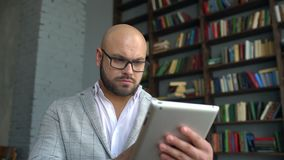 Young man in glasses using tablet pc surfing internet, young man in glasses working in tablet at home on a background of. The library. young businessman using stock video