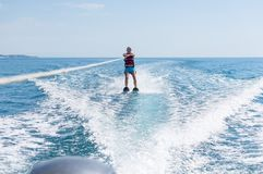 Young man glides on water skiing on the waves on the sea, ocean. Healthy lifestyle. Positive human emotions, joy. Family are spend stock photo