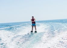Young man glides on water skiing on the waves on the sea, ocean. Healthy lifestyle. Positive human emotions, joy. Family are spend stock images