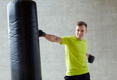 Young man in gloves boxing with punching bag Stock Photography