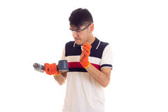 Young man with gloves and glasses holding electric screwdriver Stock Image