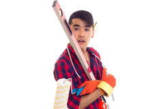Young man in gloves holding level, roll and ruler Royalty Free Stock Photo