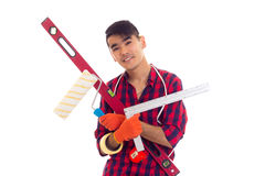 Young man in gloves holding level, roll and ruler Royalty Free Stock Photography