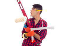 Young man in gloves holding level, roll and ruler Royalty Free Stock Image