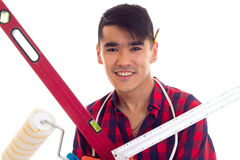 Young man in gloves holding level, roll and ruler Royalty Free Stock Photos