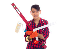 Young man in gloves holding level, roll and ruler Stock Photos