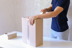 Young Man Glue Tape Box And Takes Parcel in Hands, Standing in P Stock Images