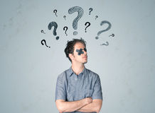 Young man with glued eye and question mark symbols Royalty Free Stock Images