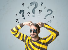 Young man with glued eye and question mark symbols Stock Photography
