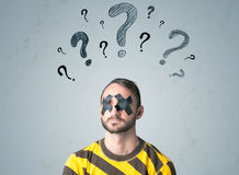 Young man with glued eye and question mark symbols Royalty Free Stock Photography