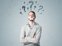 Young man with glued mouth and question mark symbols Stock Photo