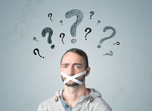 Young man with glued mouth and question mark symbols Stock Photos