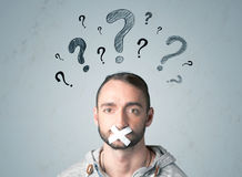 Young man with glued mouth and question mark symbols Stock Photography
