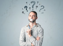 Young man with glued mouth and question mark symbols Royalty Free Stock Image