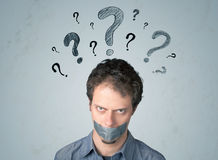 Young man with glued mouth and question mark symbols Stock Image