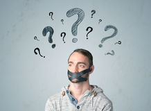Young man with glued mouth and question mark symbols. Young man with taped mouth and question mark symbols around his head Royalty Free Stock Photography
