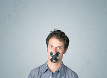 Young man with glued mouth. Young man with taped mouth. Isolated on gray background Royalty Free Stock Images