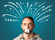 Young man with glued mouth. Young man with taped mouth and white drawn lines and arrows around his head Royalty Free Stock Image