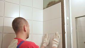 Young man gluing ceramic tile standing in bathroom indoors. stock footage