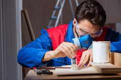 The young man gluing wood pieces together in diy concept. Young man gluing wood pieces together in DIY concept Stock Images