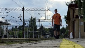 A young man goes along the railroad platform in summer in slo-mo. A young man with a crew haircut goes along the railroad platform in Ukraine on a sunny day in stock footage