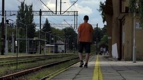 A young man goes away on a railroad platform in summer in slo-mo. A young man in an orange tshirt and black shorts goes away on a railroad platform in Uktaine in stock video footage