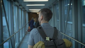 The young man goes down the hall to board the aircraft. The airport announced landing and passenger stock video footage