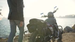 A young man goes to his motorcycle, sits on it and puts a helmet to go on a journey stock video footage