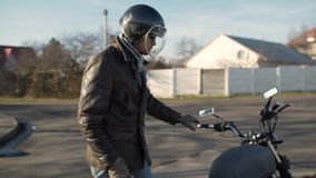 A young man goes to his motorcycle, sits on it and puts a helmet to go on a journey stock video