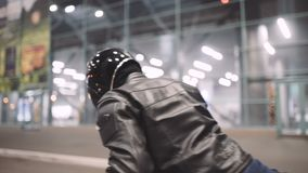 A young man goes to his motorcycle, sits on it and puts a helmet to go on a journey at night street stock video