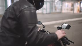 A young man goes to his motorcycle, sits on it and puts a helmet to go on a journey at night street stock footage