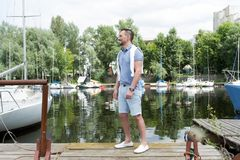 Successeful man goes to his yacht in the river bay. Attractive guy in sea marina with yacht. Summertime for sailing of young man. Young man goes to his yacht in Royalty Free Stock Image