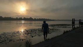 Young man goes to a picturesque riverbank at a splendid sunset in slow motion stock video footage