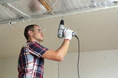 Young man in goggles fixing drywall suspended ceiling to metal frame using electrical screwdriver on ceiling insulated with shiny stock photography