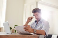 Young man going through paperwork at home office Royalty Free Stock Photos