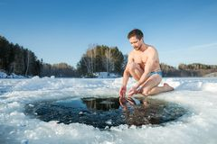 Young man going to swim in an ice hole royalty free stock images