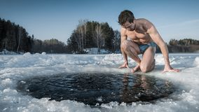 Young man going to swim in an ice hole stock photo