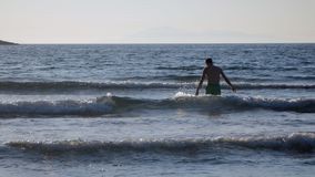 Young man is going to swim in the sea. But it is not getting deeper stock video footage