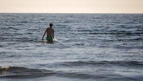 Young man is going to swim in the sea. But it is not getting deeper. Fast motion stock video footage