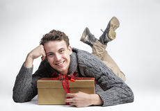 Young man with gold gift box. Young man laying on the floor wearing a grey sweater offering a gold gift box with a red plaid ribbon Stock Images