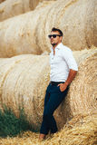 Young man good looks in sunglasses at the straw. The guy in the white shirt and sunglasses posing at the straw stack. Series stock photography